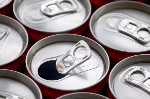 Beaucoup de canettes de soda en aluminium. publicité pour la fabrication en série de boissons gazeuses ou de boîtes de conserve