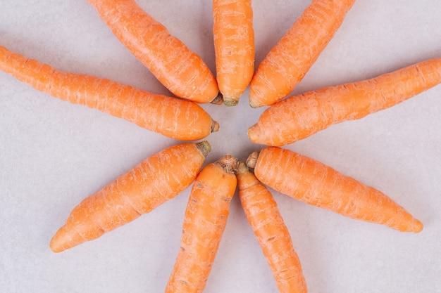 Beaucoup de carottes fraîches sur une surface blanche