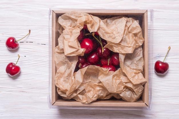 Beaucoup de cerise dans une boîte en carton kraft sur table en bois