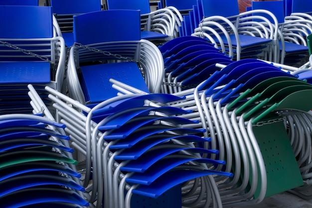 Beaucoup de chaises colorées empilées en plein air