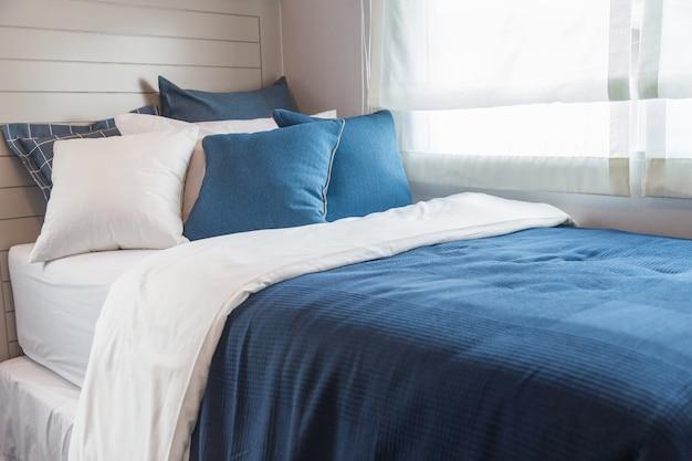 Beaucoup de chambre bleue et blanche avec la lumière chaude de la fenêtre.