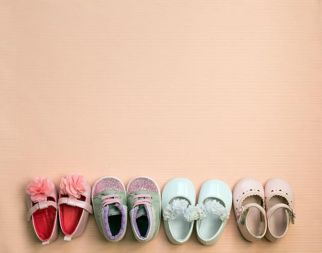 Beaucoup de chaussons bébé mignon placés sur fond rose, vue de dessus