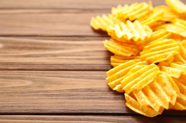 Beaucoup de chips de pommes de terre préparées snack sur mur brun