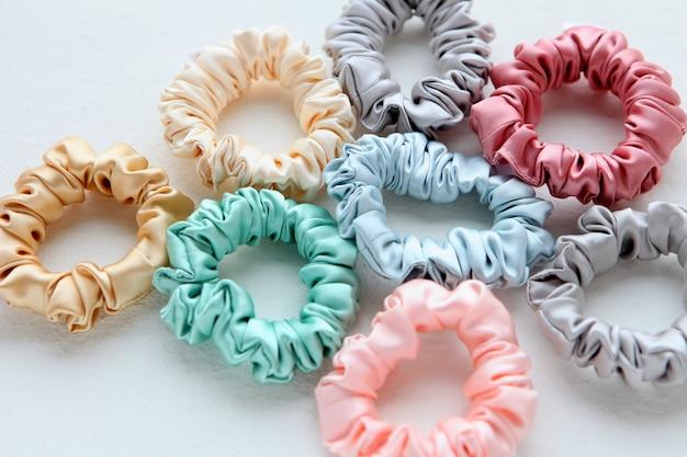 Beaucoup de chouchous en soie colorés sur des bandeaux en plastique layof blancs