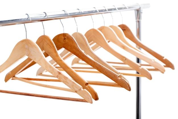 Beaucoup de cintres vides en bois pour vêtements sur support sur fond blanc. vous n'avez rien à porter. vente