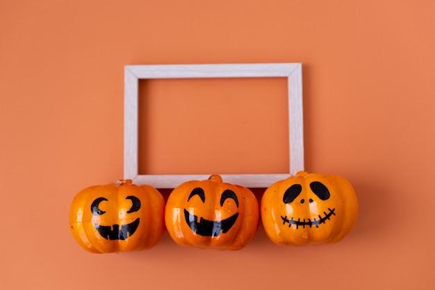 Beaucoup de citrouilles d'halloween dans une rangée sur fond orange