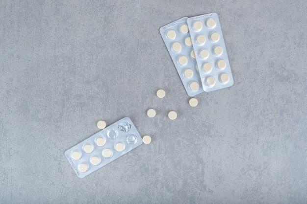 Beaucoup de cloques avec des pilules blanches sur une surface grise