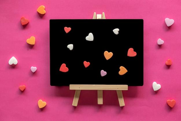 Beaucoup de cœurs dans le tableau noir sur fond rose, icône de l'amour, saint valentin