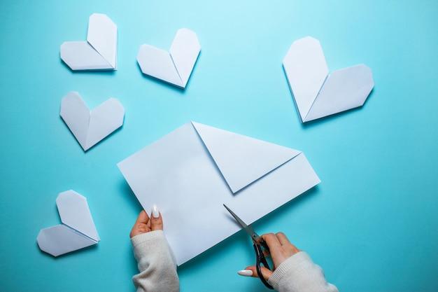 Beaucoup de coeurs en origami blanc sur fond bleu avec une feuille de papier et des ciseaux au centre. carte de saint valentin avec femme faisant coeur origami sur fond bleu.