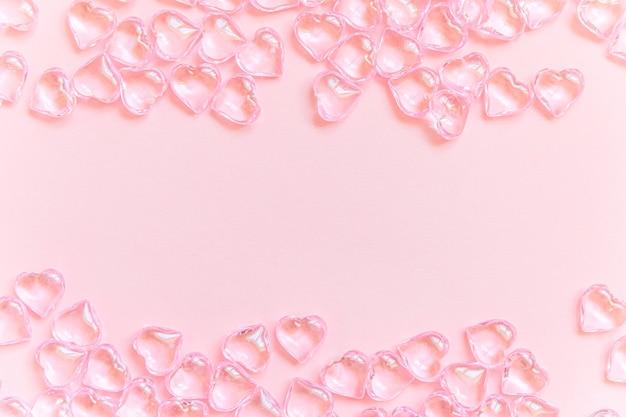 Beaucoup de coeurs roses isolés sur fond pastel rose, cadre de bordure