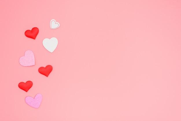 Beaucoup de coeurs rouges et roses regroupés sur un rose romantique
