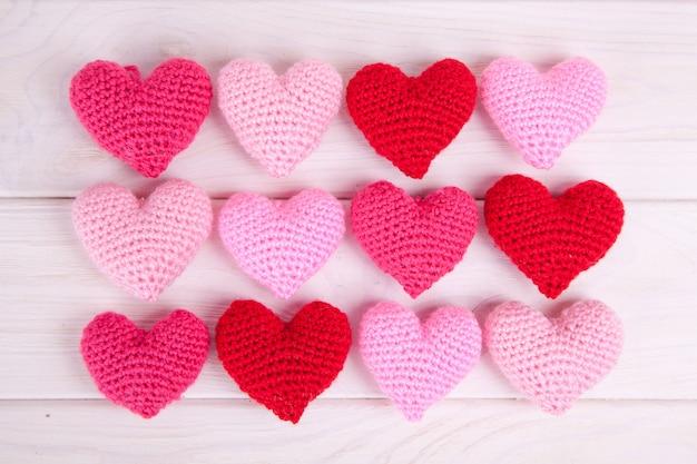Beaucoup de coeurs tricotés roses sur un fond en bois blanc. la saint valentin.