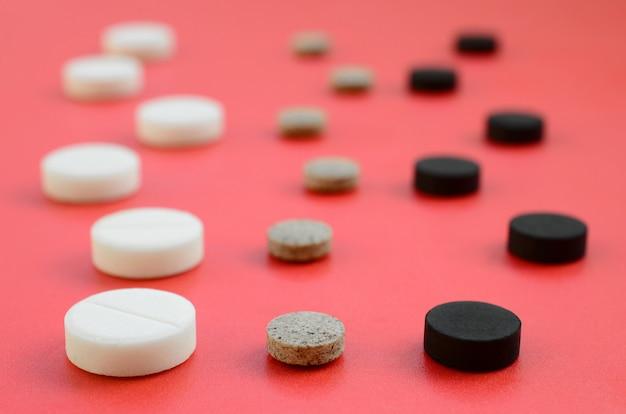 Beaucoup de comprimés blancs, noirs et marron se trouvent sur la surface rouge