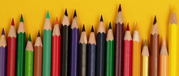 Beaucoup de couleurs de bois empilées pour créer des illustrations sur du papier de fond jaune.