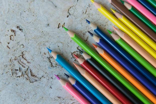 Beaucoup de crayons de couleur sur fond de liège naturel clair.