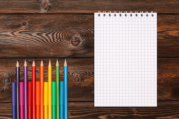 Beaucoup de crayons et crayons de couleurs assorties avec carnet
