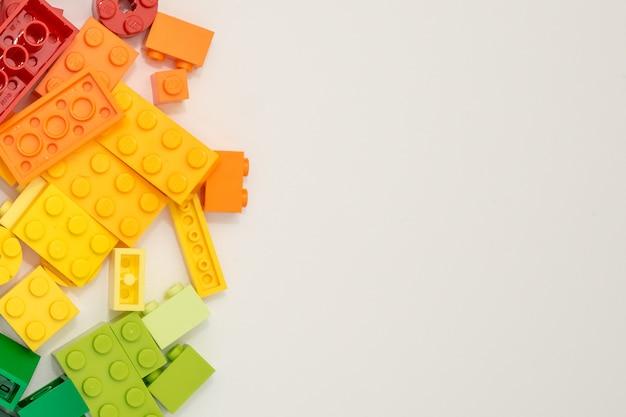 Beaucoup de cubes de constructeur en plastique sur fond blanc. jouets populaires.