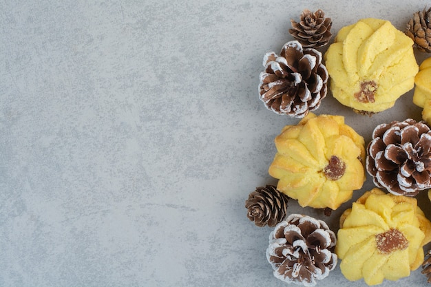 Beaucoup de délicieux biscuits frais avec de petites pommes de pin sur un tableau blanc.