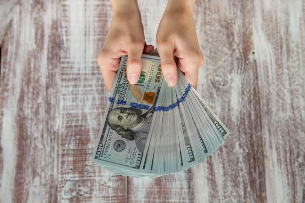 Beaucoup de dollars tombant sur la main d'une femme avec de l'argent