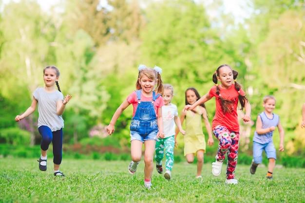 Beaucoup d'enfants, de garçons et de filles différents qui courent dans le parc le jour d'été ensoleillé dans des vêtements décontractés