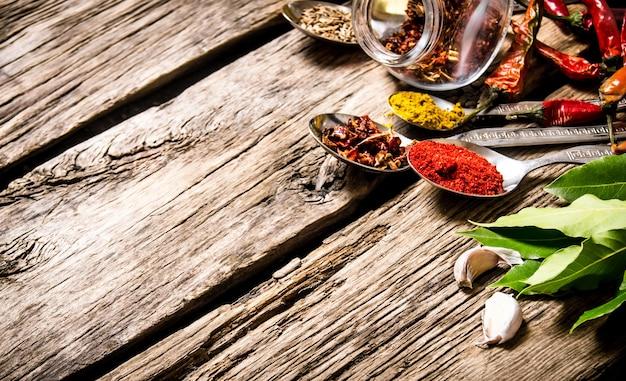 Beaucoup d'épices différentes dans des cuillères avec des herbes et de l'ail sur une table en bois.