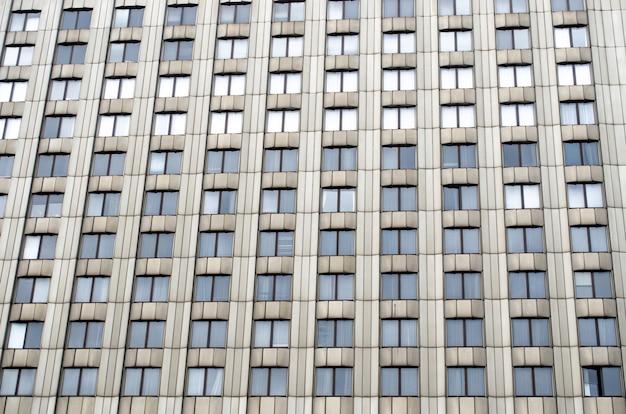 Beaucoup de fenêtres un grand bâtiment urbain de couleur monophonique.