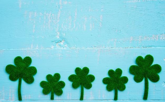 Beaucoup de feuille de trèfle de papier vert sur fond de table en bois blanc et bleu