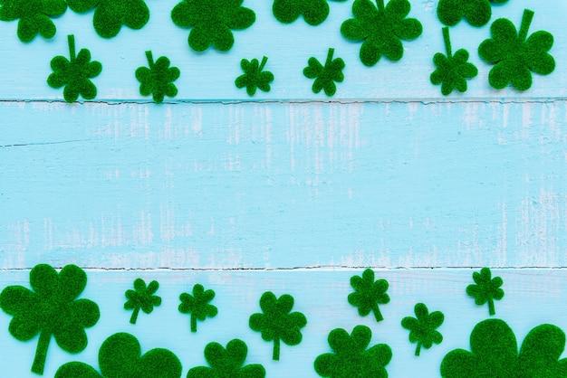 Beaucoup de feuille de trèfle de papier vert sur table en bois blanc et bleu pastel