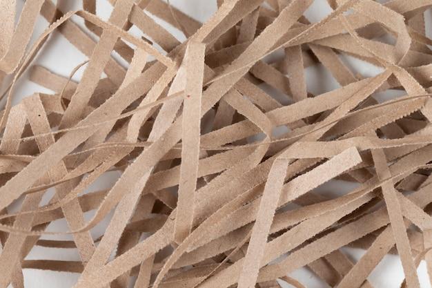 Beaucoup de fines bandes de papier beige. morceaux de papier décoratifs pour cadeaux sur fond blanc