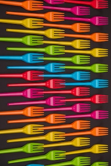 Beaucoup de fourchettes en plastique de couleur sur un fond clair