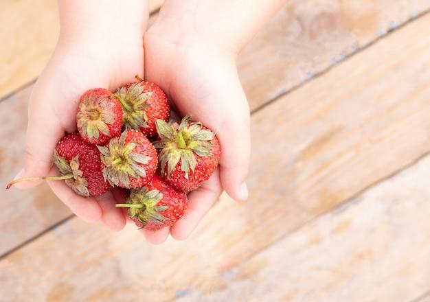 Beaucoup de fraises dans la paume des enfants, au-dessus de la table en bois