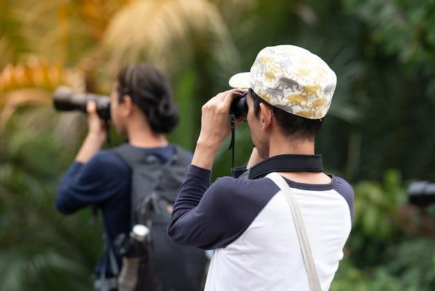 Beaucoup de gens utilisent des caméras pour faire briller quelque chose dans le parc.