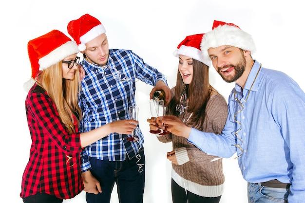 Beaucoup de jeunes femmes et hommes buvant à la fête de noël sur fond de studio blanc