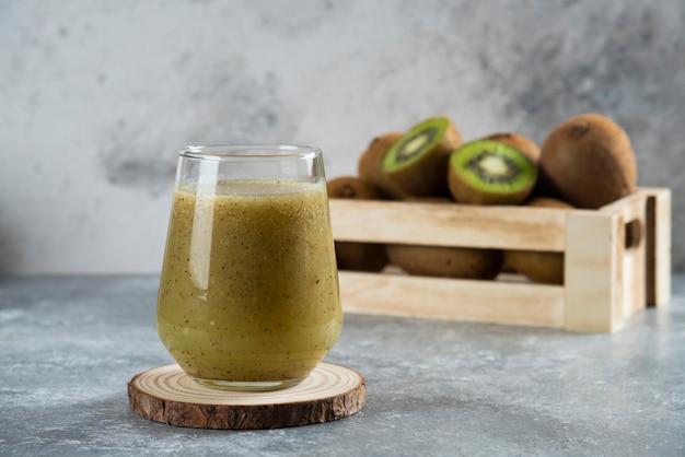 Beaucoup de kiwis dans un panier en bois avec une tasse en verre de jus.