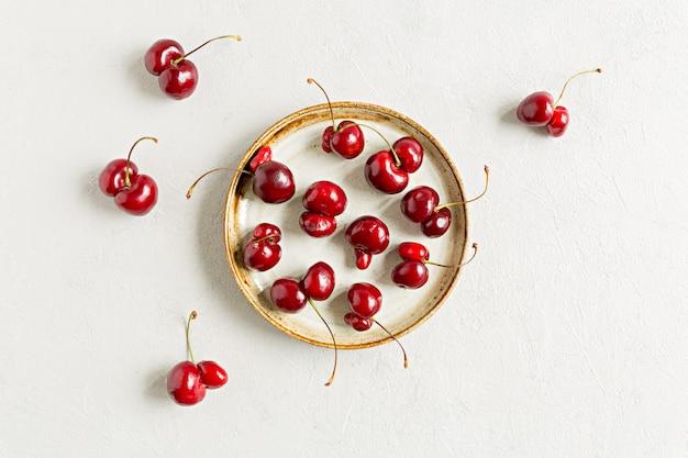 Beaucoup de laides cerises aux fruits rouges à plat poser sur fond blanc sur plaque