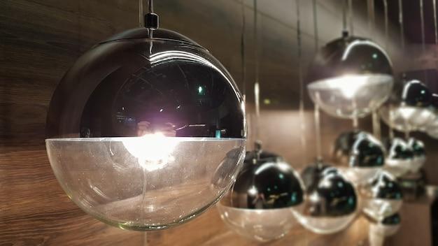 Beaucoup de lampes rondes près d'un mur marron en bois. lumières rondes à l'intérieur. contexte pour la conception. ampoules décoratives.