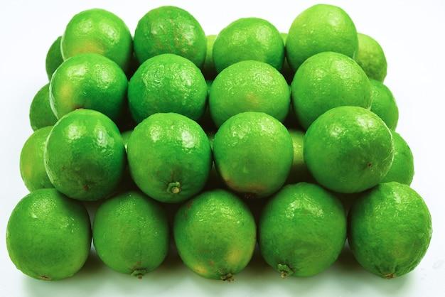 Beaucoup de limes fraîches sur fond blanc.