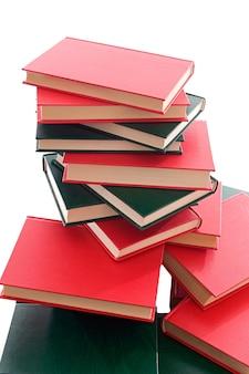 Beaucoup de livres rouges et verts empilés sur un fond blanc