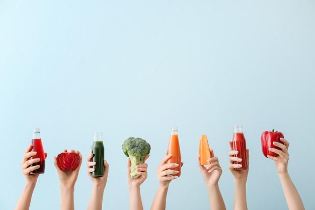 Beaucoup de mains avec des bouteilles de jus de légumes en couleur