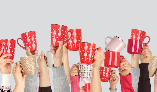 Beaucoup de mains levées avec des tasses en céramique sur un blanc