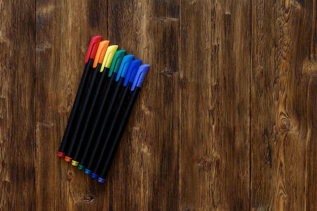 Beaucoup de marqueurs de couleurs arc-en-ciel assortis, bois copyspace