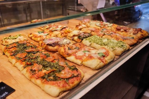Beaucoup de mini pizzas sur le comptoir. différents types de pizzas sont proposés en grande quantité