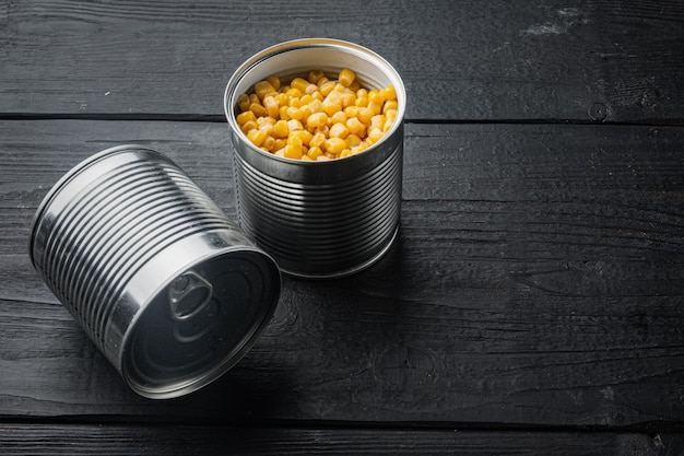 Beaucoup de morceaux de maïs jaune en conserve dans une boîte en métal, sur fond de table en bois noir avec espace de copie pour le texte