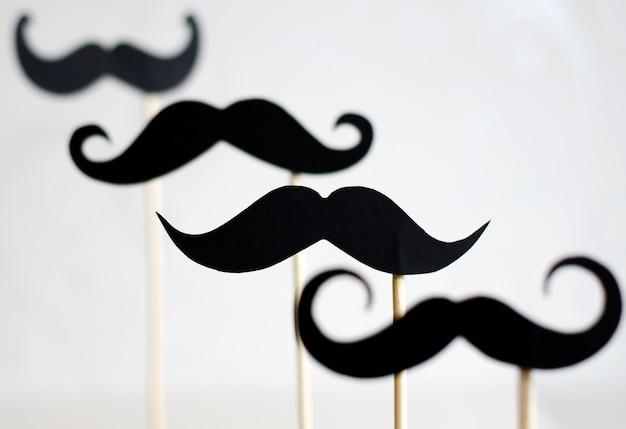 Beaucoup de moustaches de papier noir sur des bâtons