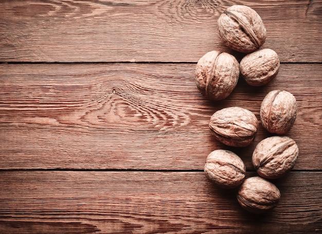 Beaucoup de noix dans une coquille sur une table en bois. copiez l'espace. vue de dessus.