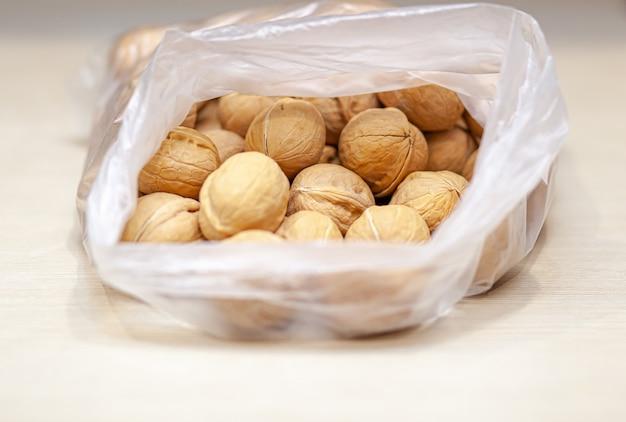 Beaucoup de noix entières dans un sac sur fond blanc. aliments sains et biologiques avec une teneur élevée en protéines et en protéines.