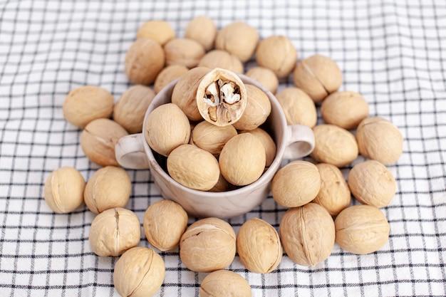 Beaucoup de noix entières dans une tasse sur une serviette en gros plan. aliments sains, biologiques et sains avec une teneur élevée en protéines et en protéines.