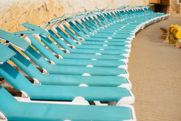 Beaucoup de nouvelles belles chaises longues bleues se trouvent près de la piscine de l'hôtel par une journée ensoleillée. bonnes vacances vacances. vacances d'été et tourisme.