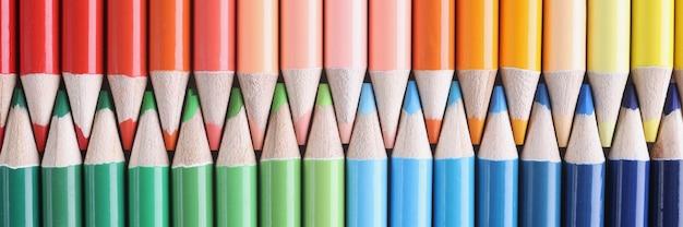 Beaucoup de nuances de crayons en bois multicolores pointus se trouvant dans des couleurs de fond de plan rapproché d'arc-en-ciel