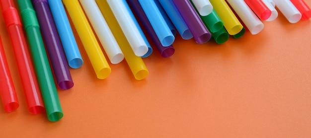 Beaucoup de pailles colorées pour les boissons se trouve sur une surface de fond orange vif